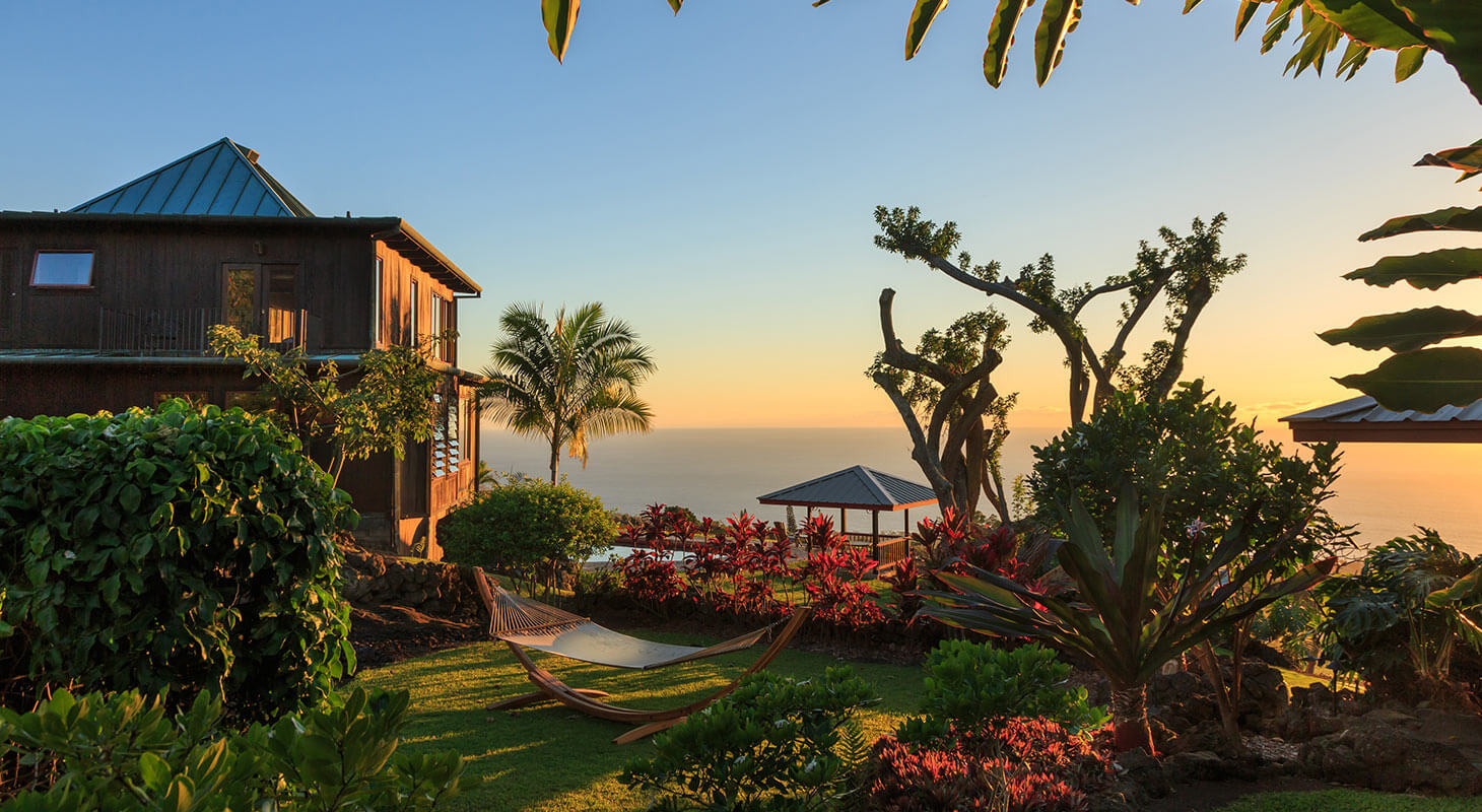 Holualoa gardens at sunset with hammock, flowers, and inn building